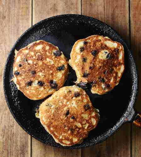 3 blueberry pancakes on top of large pan.