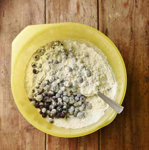 Blueberries and flour mixture in large yellow bowl with spoon.