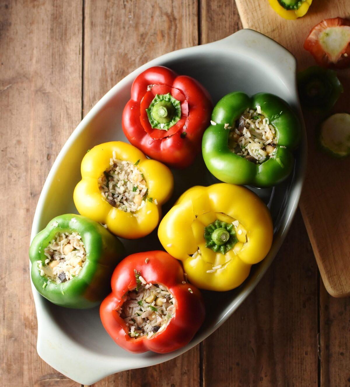 6 tri-coloured stuffed peppers in casserole dish.
