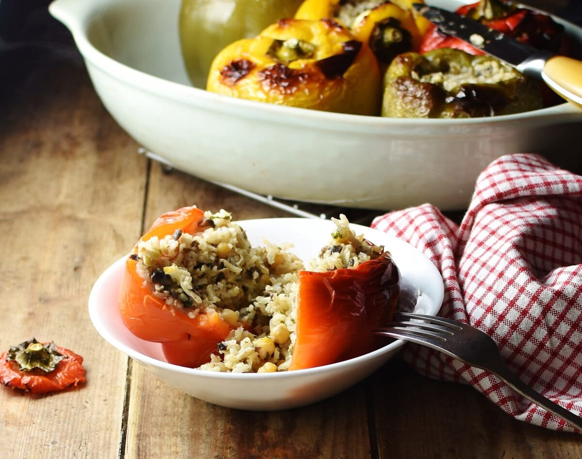 Stuffed red pepper with rice, cut open, with red-and-white checkered cloth to the right and stuffed peppers in dish in background.