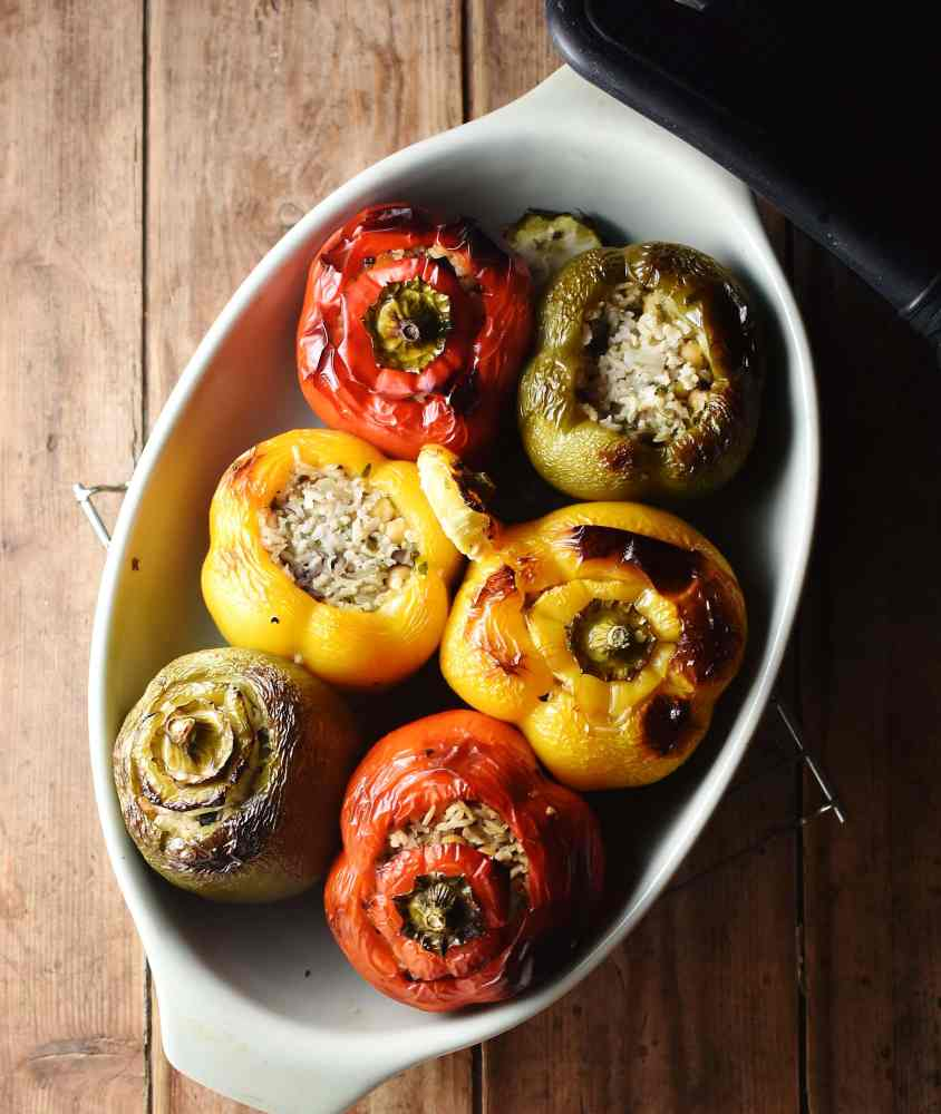 Top down view of baked tri-coloured stuffed peppers in oval dish.