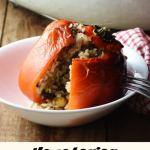 Stuffed red pepper in white bowl with stuffed peppers in dish in background.