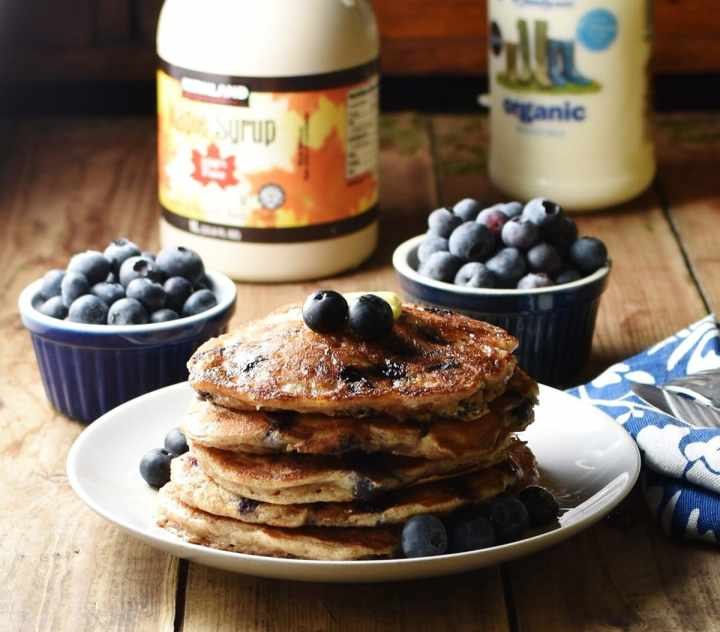 Side view of blueberry pancakes stacked up on white plate, with blueberries in 2 blue dishes, bottle of maple syrup and bottle of milk in background.