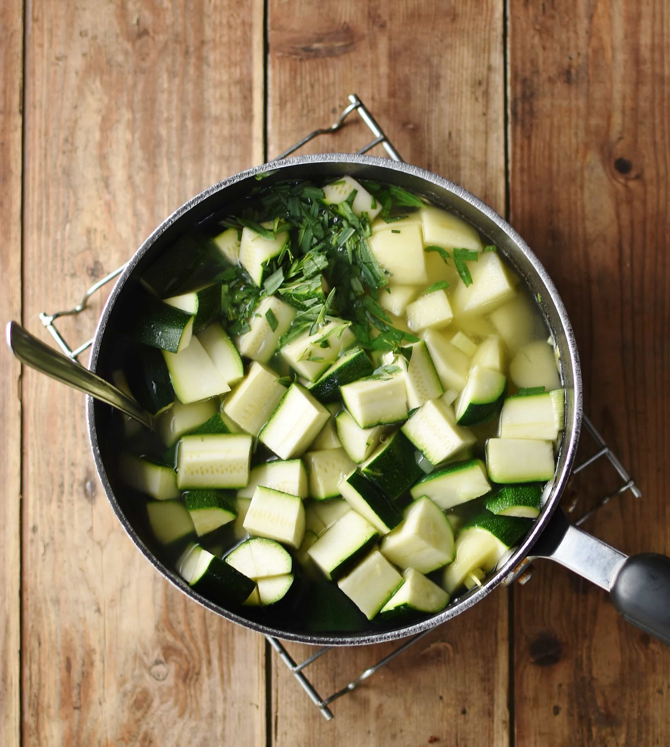 Cubed zucchini, potatoes and herbs in large pot filled with water.
