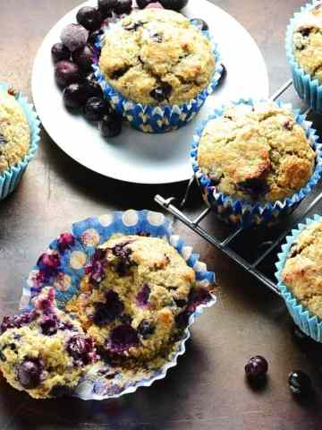 Top down view of blueberry muffins on oven tray with small white plate and cooling rack.