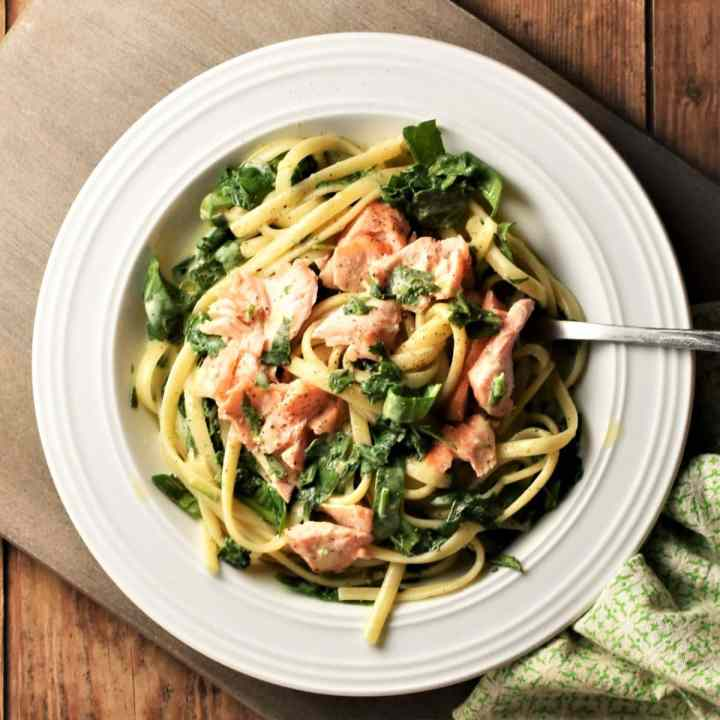 Salmon and spinach with pasta and creamy sauce in white bowl with fork.