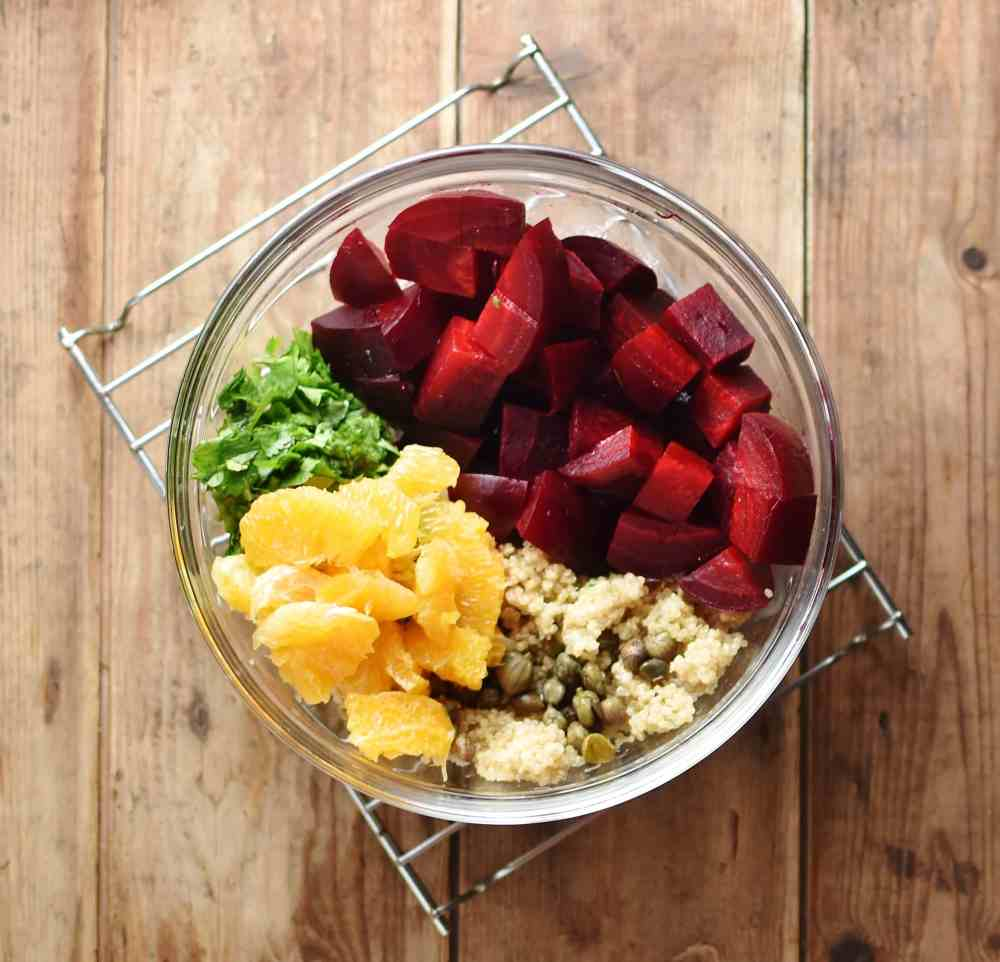Top down view of cubed beetroot, orange pieces, herbs and cooked quinoa inside translucent bowl.
