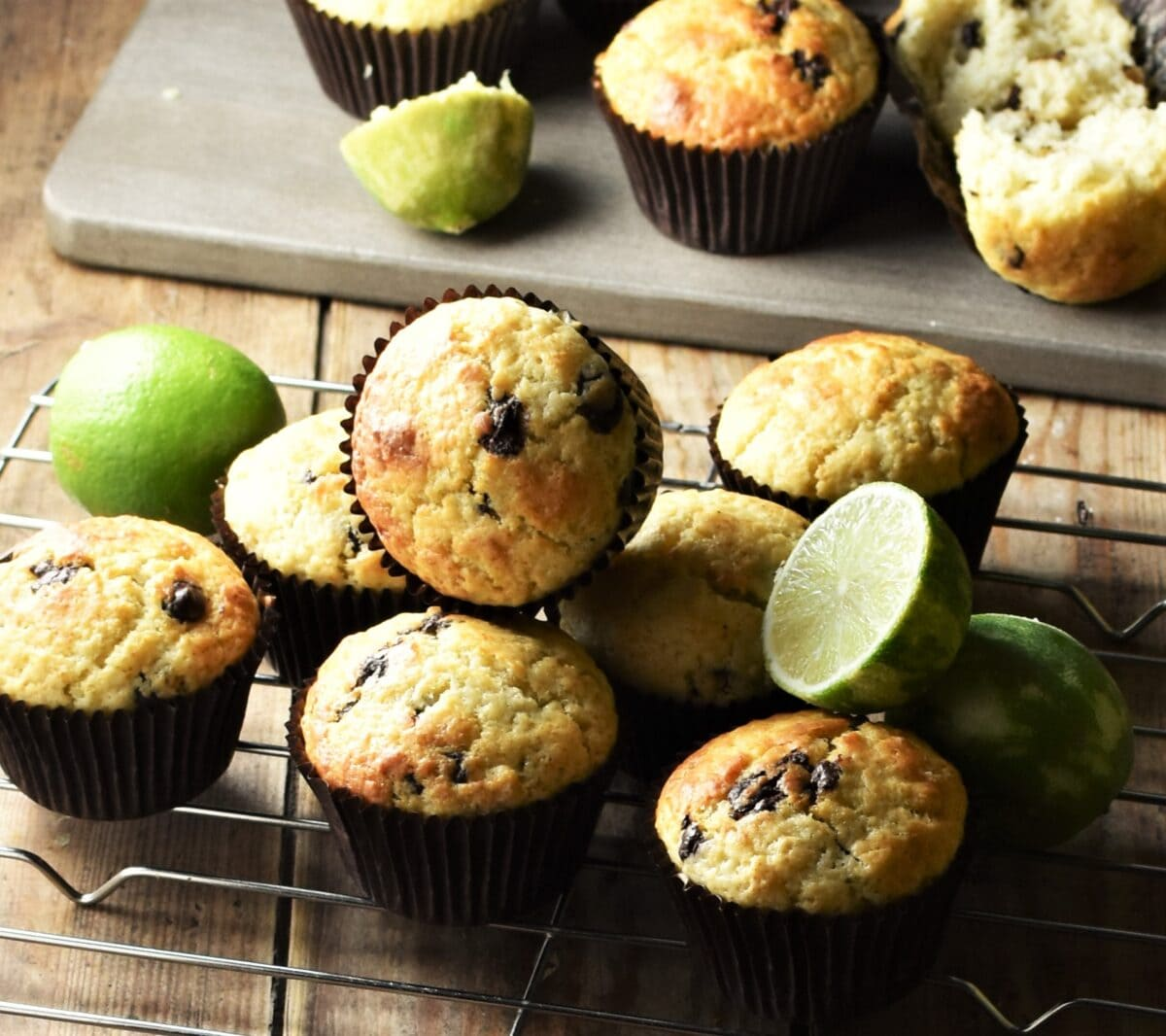 Muffins with chocolate chips in brown cases and limes on rack and grey wooden board in background.
