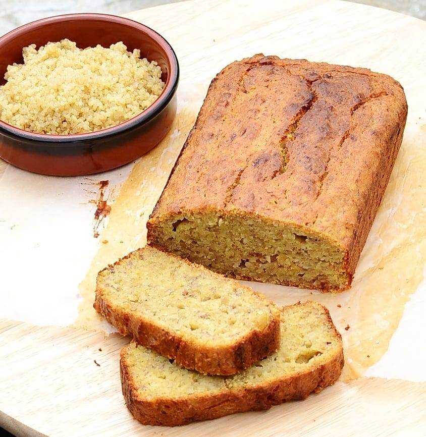 Banana bread on top of baking paper with cooked quinoa in round brown dish on top of light wooden surface.