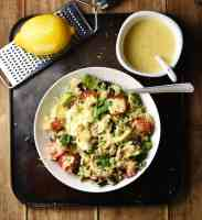 Quinoa vegetable salad in white bowl with spoon, creamy dressing in white dish with spoon in top right and zester with lemon in top left corners.