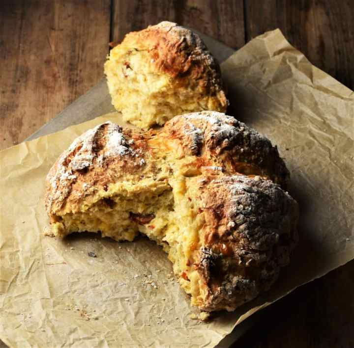 Sun dried tomato soda bread with piece broken off on top of parchment.
