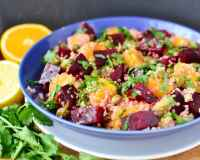 Side view of beets quinoa salad in blue bowl on white plate, with herbs and oranges in background.