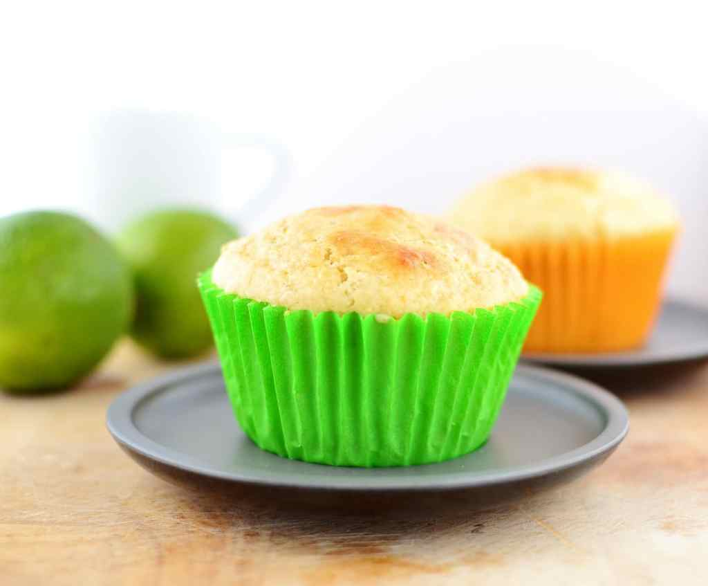 Side view of lime muffins in green paper case on grey plate with limes in background.