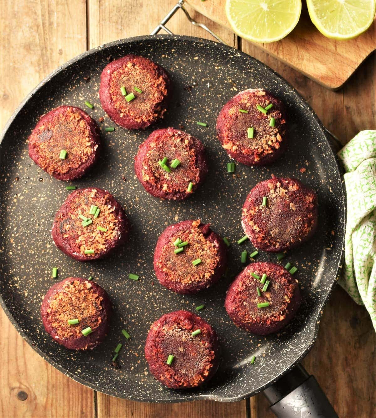 Fried beetroot cakes on top of large pan with lemon in background.