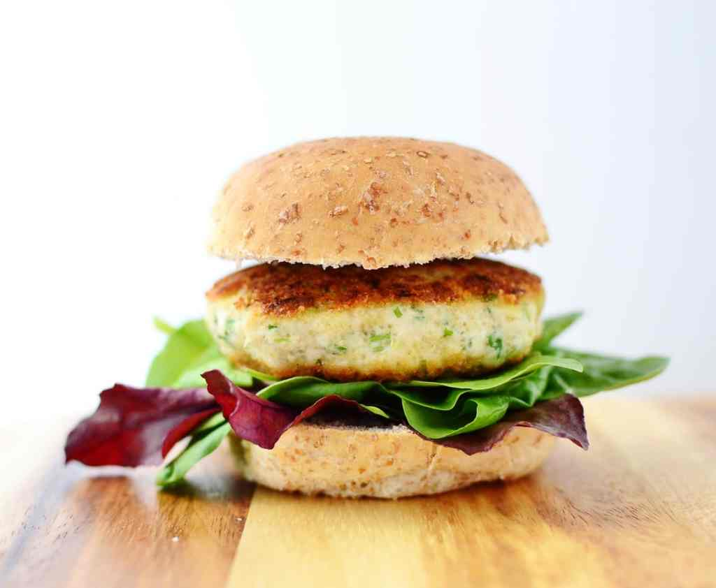 Side view of chicken burger with salad leaves inside wholewheat bun on top of wooden surface.