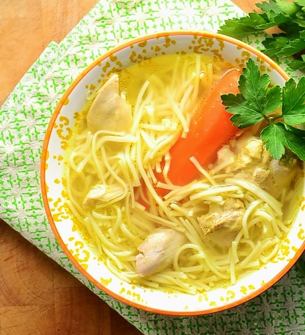 Top down view of chicken noodle soup with carrot and parsley inside yellow-and-white bowl, on top of green cloth.