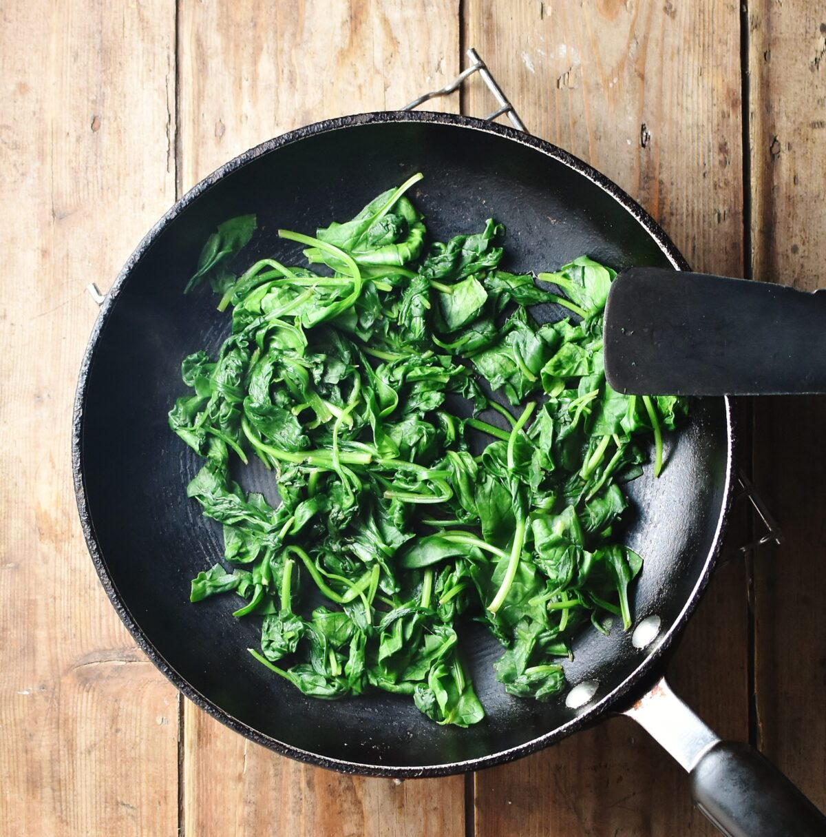 Wilted spinach in black pan.