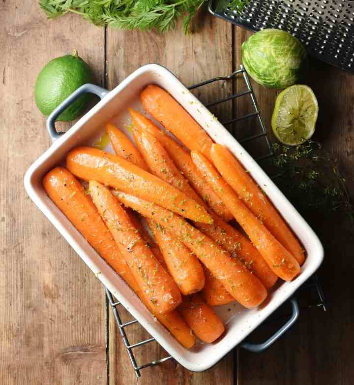 Top down view of braised carrots in white rectangular dish, with limes in background.