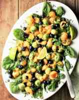 Top down view of cantaloupe salad with spinach and avocado on white oval plate with spoon.