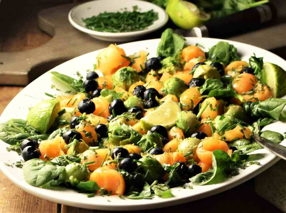Side view of cantaloupe, spinach, blueberry and avocado salad on white plate.