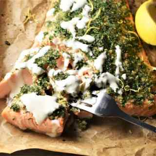 Close-up view of salmon with herbs and creamy sauce on top of parchment.