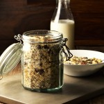 Homemade muesli in open jar, with bottle of milk and muesli in bowl in background.