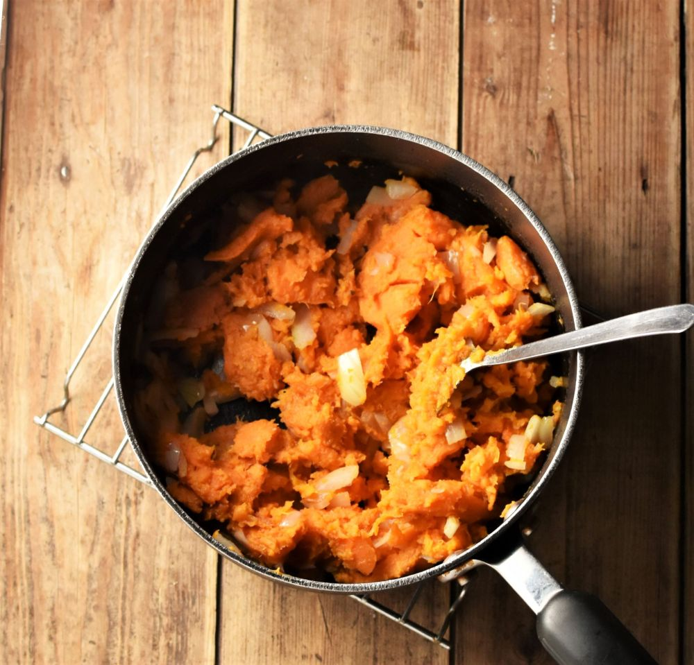 Sweet potato mash with chopped onions in large pot with spoon.