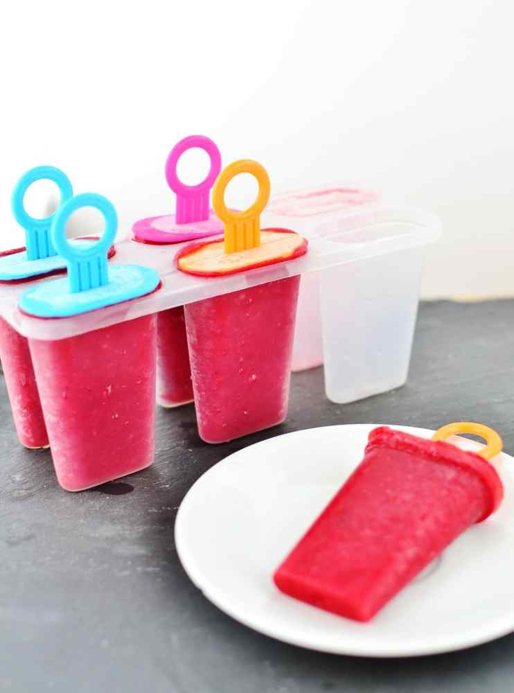 Rooibos raspberry ice pops on small white plate and in plastic mold.