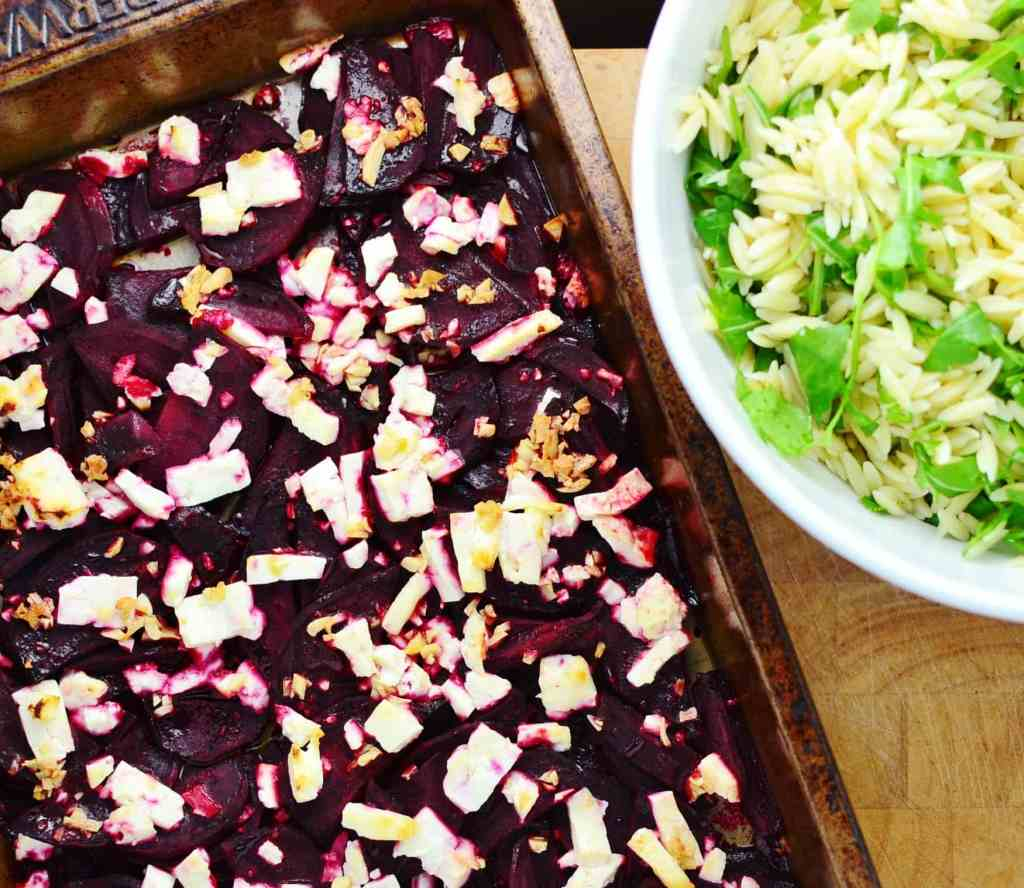 Top down view of baked beetroot and feta on top of oven tray and orzo with arugula in white bowl.