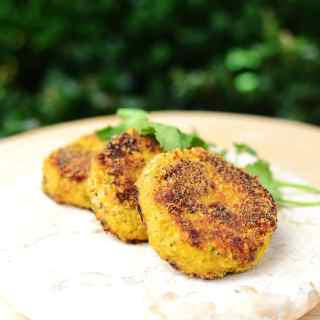 Cauliflower patties on marble plate with bushes in background.