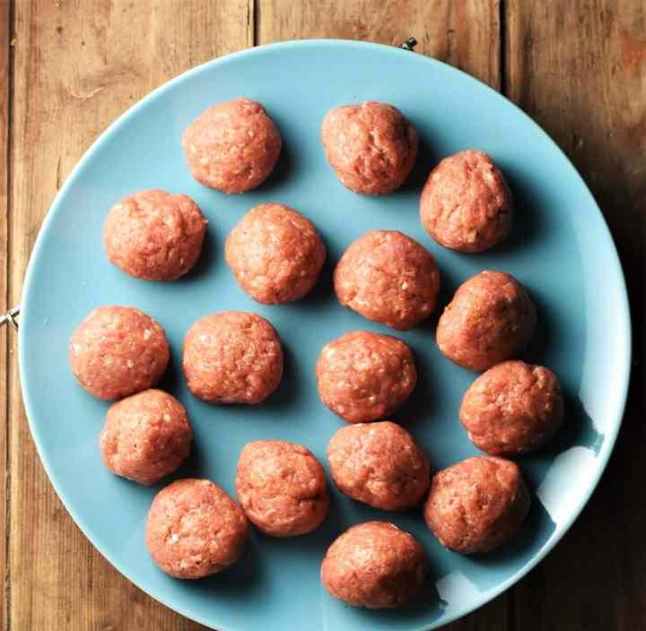 Raw meatballs on blue plate.