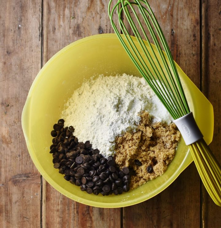 Flour, chocolate chips and sugar in large yellow bowl with green whisk.