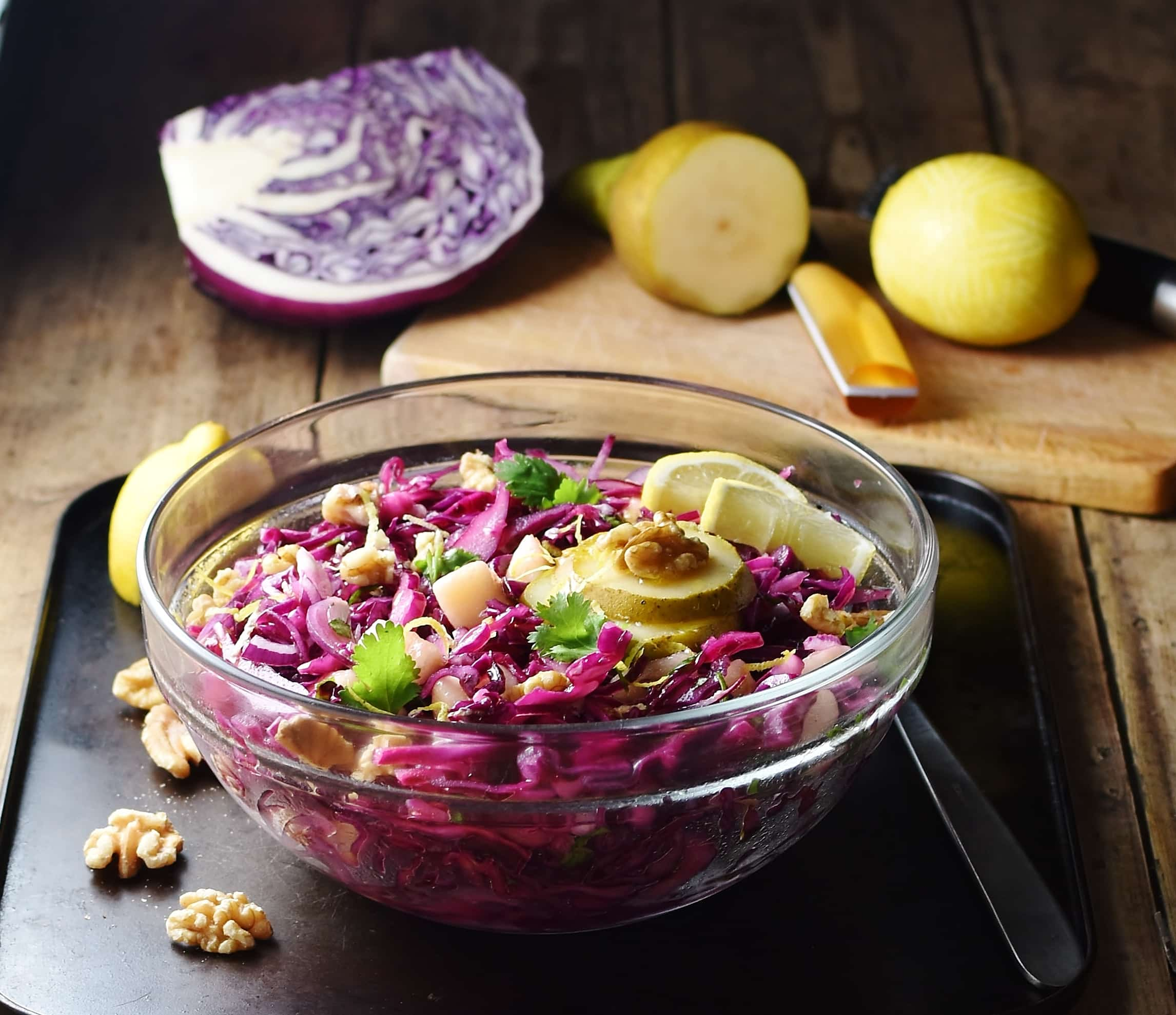 Shredded red cabbage with pear, walnuts and herbs in mixing bowl with spoon to the right, lemon ,pear, red cabbage piece and knife in background.