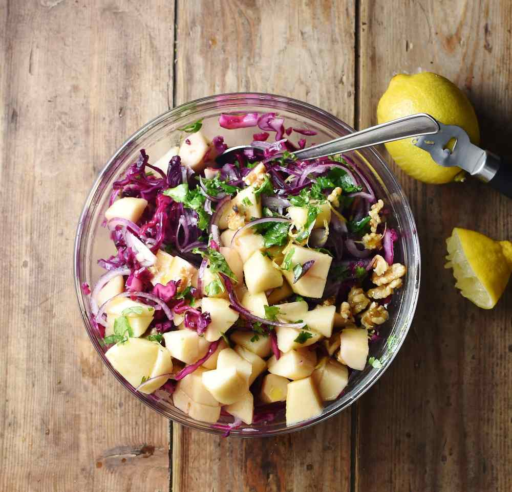 Chopped pear, walnuts, herbs and red cabbage in mixing bowl with spoon and lemons to the right.