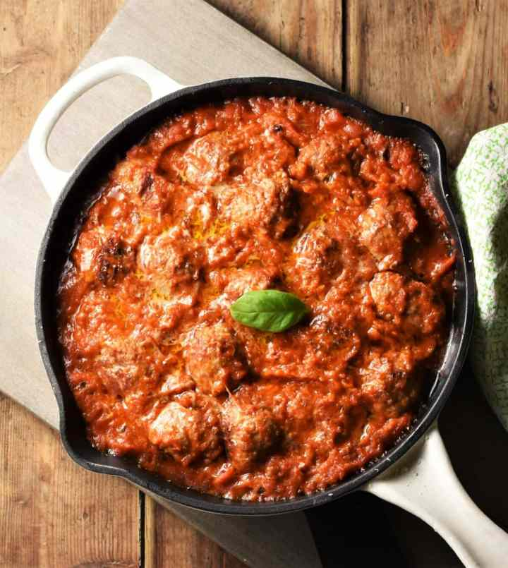 Meatballs in tomato sauce in pan on top of grey wooden board.