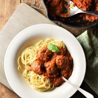 Meatballs in tomato sauce over spaghetti in bowl with fork and meatballs in sauce in pan in top right corner.
