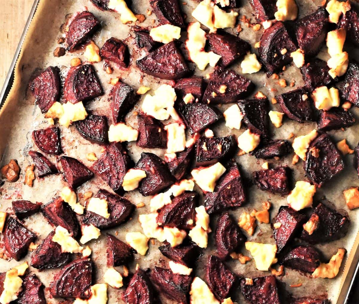 Roasted beet wedges and crumbled feta on baking sheet.