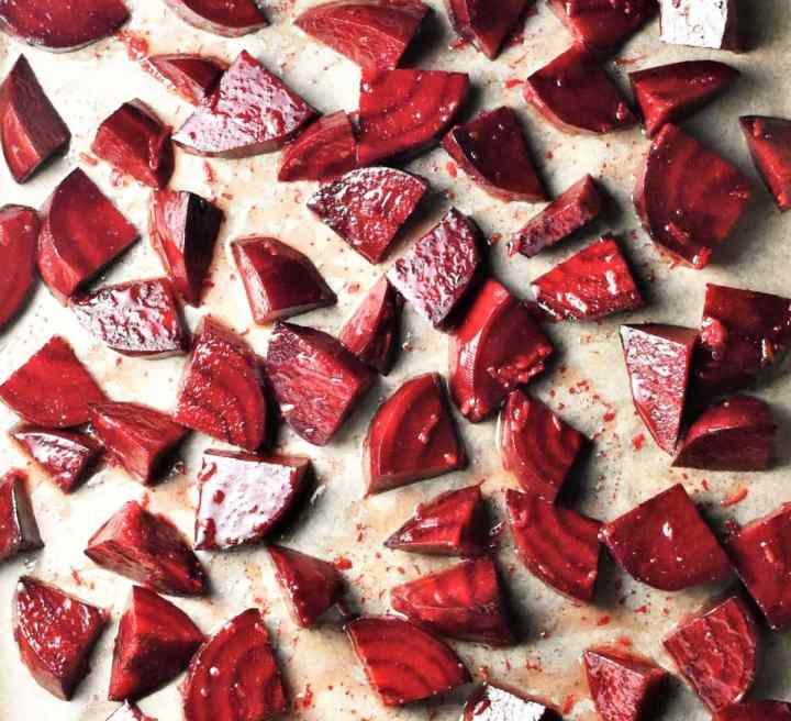 Small beetroot wedges coated in oil on top of parchment.