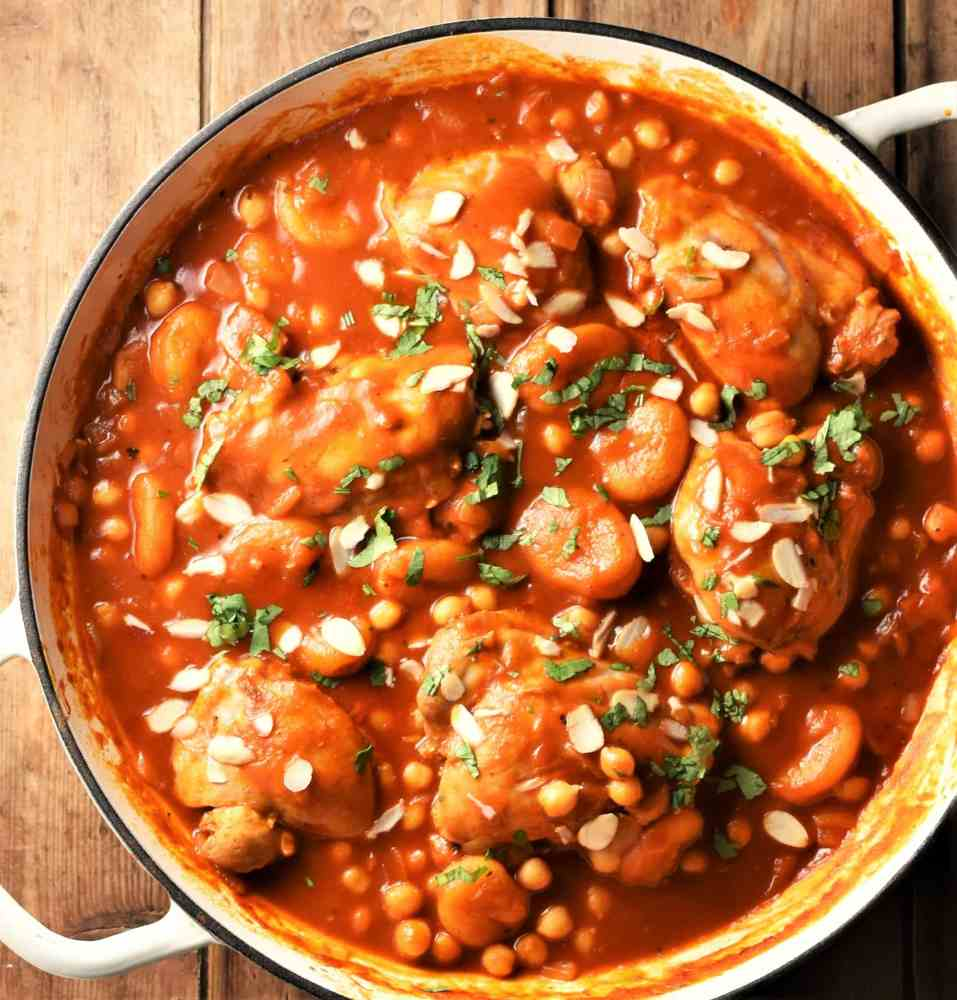 Chicken with chickpeas in tomato sauce with almond flakes in shallow white dish.