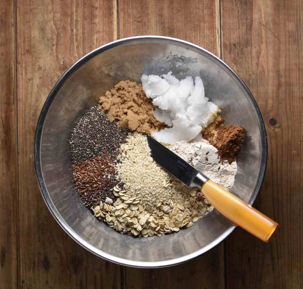Crumble topping ingredients with small knife in metal bowl.