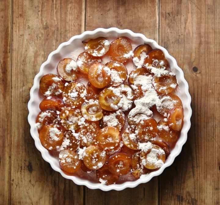 Plums with flour in white pie dish.