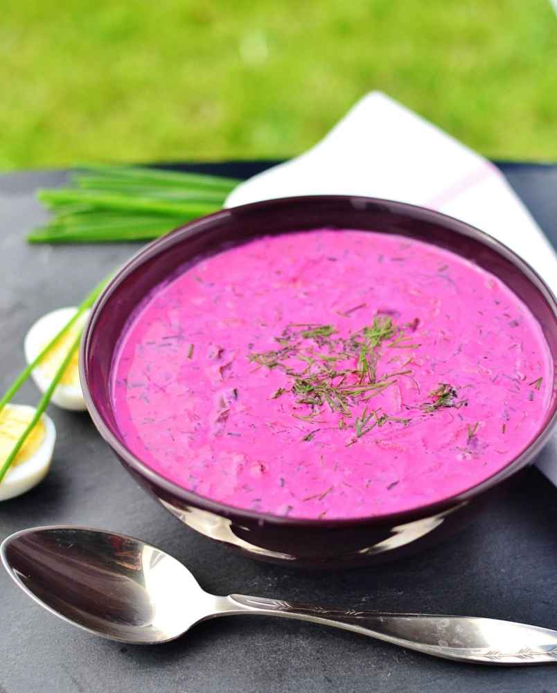 Beet soup garnished with dill in purple bowl with spoon in front, halved eggs, chives and white cloth in background.