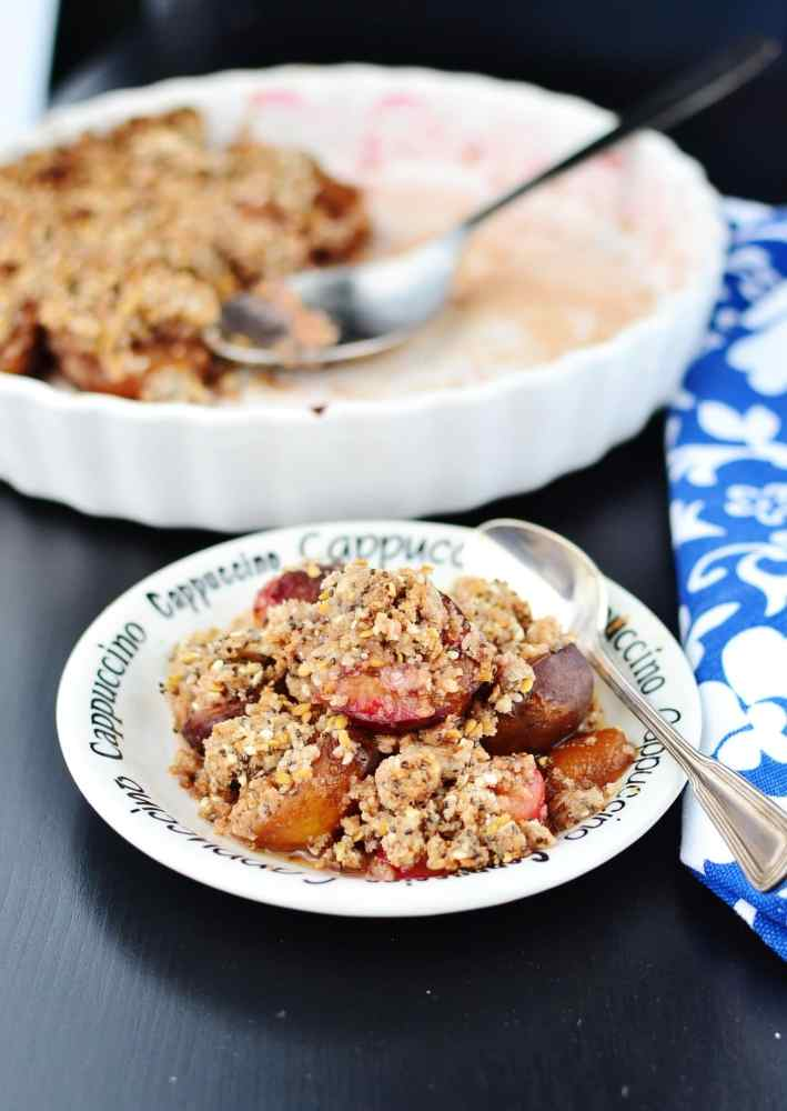 Plum crumble on small white plate with spoon, blue-and-white cloth and white pie dish in background.