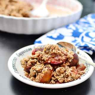 Side view of plum crumble on small white plate with spoon, blue-and-white cloth and white pie dish in background.