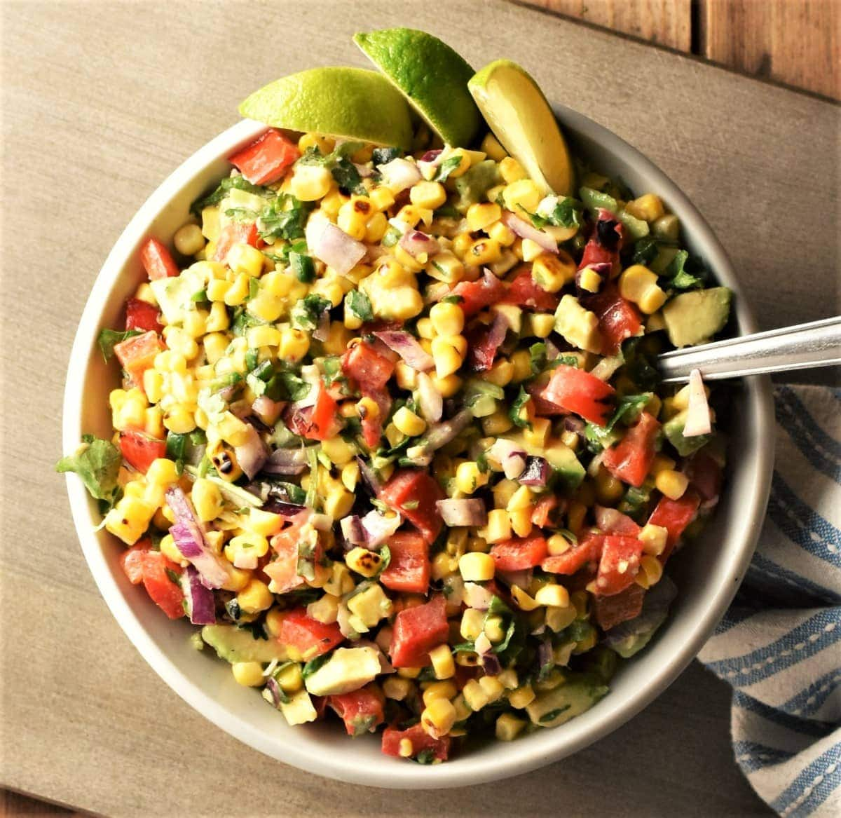 Top down view of corn salsa with lime wedges in bowl with spoon.