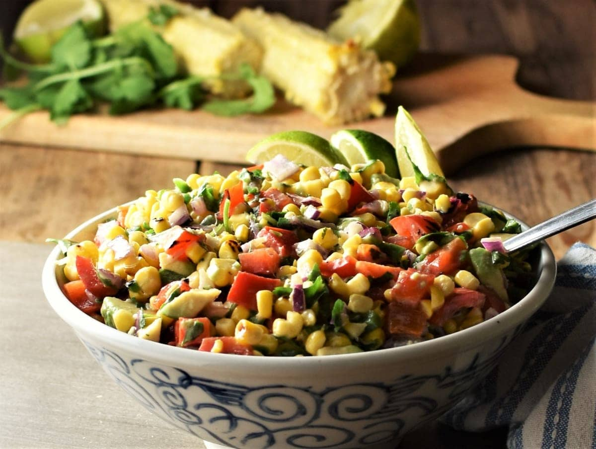 Side view of corn salsa with vegetables in bowl, with corn on cob and herbs in background.