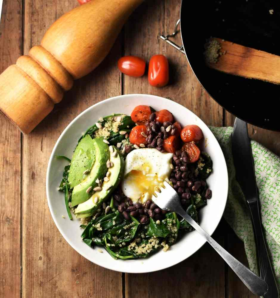 Quinoa and spinach mixture with avocado slices, cherry tomatoes, egg and beans in white bowl with fork, tomatoes, pepper grinder, green cloth with knife and skillet in background.