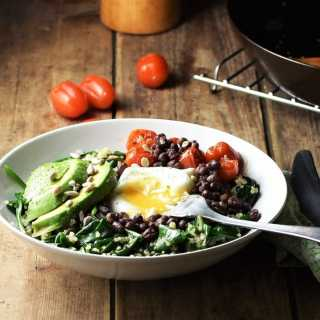 Side view of quinoa breakfast bowl with spinach, sliced avocado, egg, baby tomatoes and fork, with tomatoes, skillet and green cloth with knife in background.