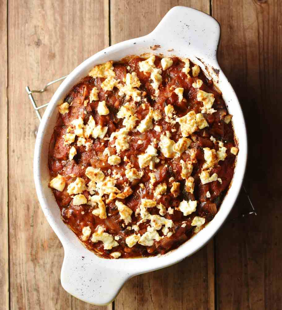 Tomato casserole with crumbled feta on top inside white oval dish.