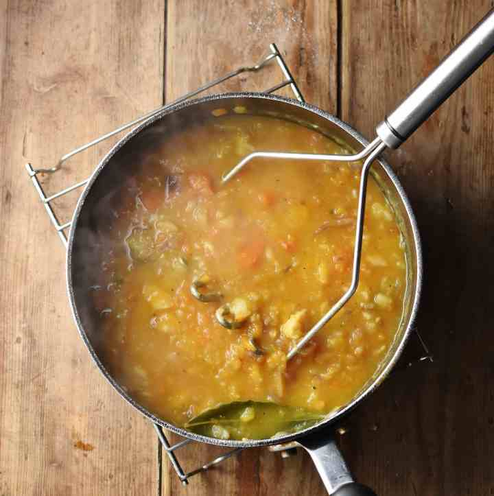 Chunky thick soup with potato masher in large pot on cooling rack.